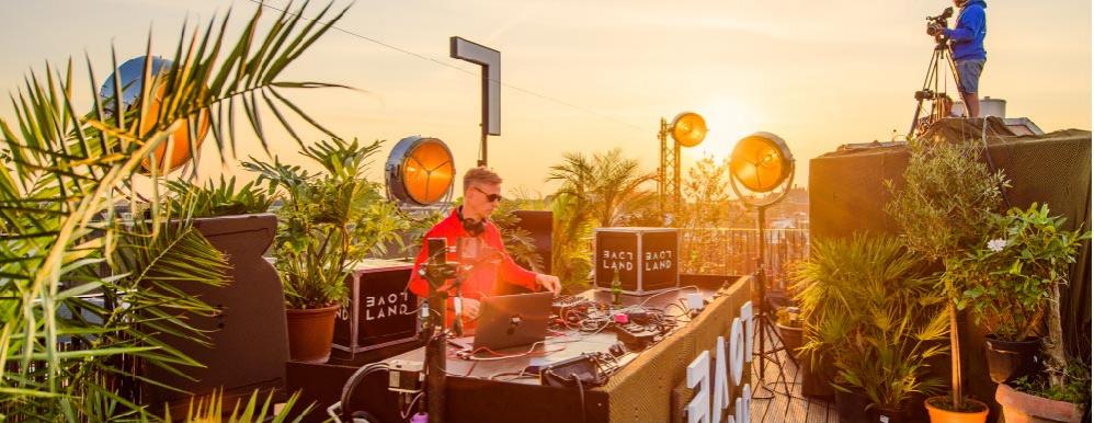 Loveland Rooftop Sessions met dj op het dak in Amsterdam terwijl de zon ondergaat lekkere techno beats maken op Koningsdag 2020